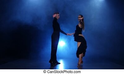 Happy couple dancing jive in smoky studio with blue...