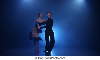 Happy couple dancing rumba in smoky studio with blue...