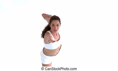 Healthy woman doing a yoga pose against white background