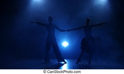 Silhouette of pair dancers performing samba dance in smoky studio
