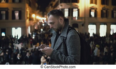 Young handsome tourist man standing in the crowd in evening. Male use the smartphone to finds direction.