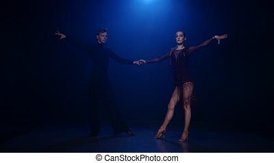 Salsa dancing couple of professional elegant dancers on blue...