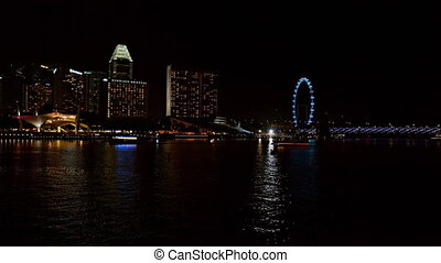 Night time cityscape of Singapore with ferry boat traffic -...