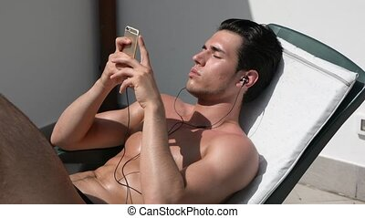Shirtless muscular young man sunbathing, listening to music