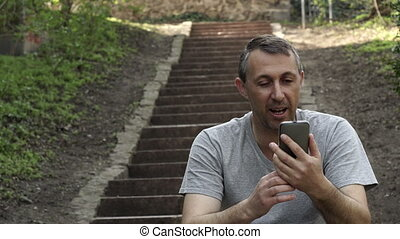 Man In Video Call Outdoor On Stairs Person Walks By - Middle...