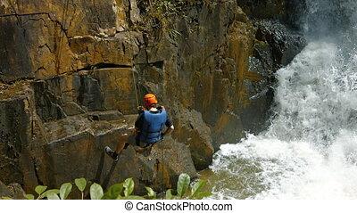 Adventurous tourist rappels into the river beneath Datanla...