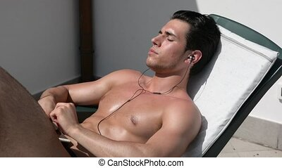Shirtless muscular young man sunbathing, listening to music