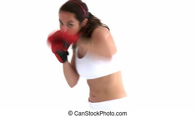 Confident woman with boxing gloves against a white...
