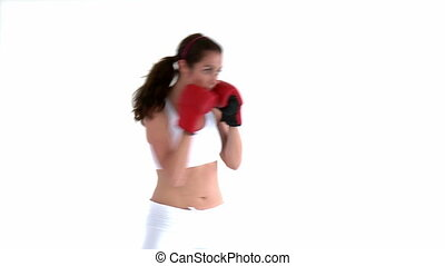 Sporty woman doing boxing exercises against a white...