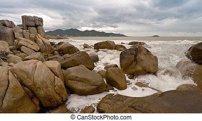 Ocean Waves and Foam amongst Enormous Boulders in Vietnam -...
