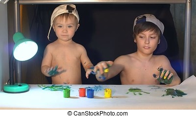 Two boys draw color paints on the paper with fingers