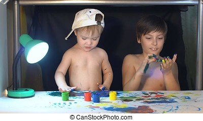Two boys draw color paints on the paper with my fingers.