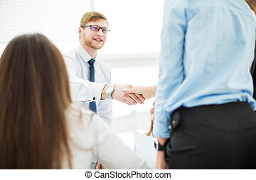 Bank Manager and the customer shake hands after signing a...