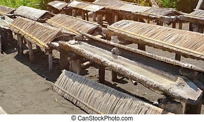 Troughs of Brine Drying in the Sun to Produce Edible Salt -...