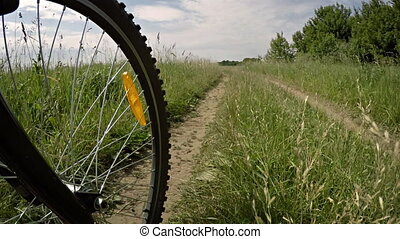 Bicycle riding in a meadow. Wheel in motion close up.
