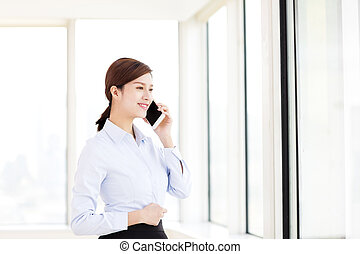 smiling business woman talking on the phone in  office