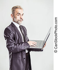 portrait in full growth - experienced businessman with an open laptop on a white background