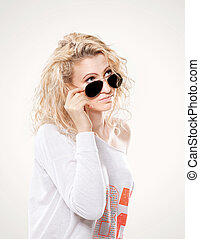 beautiful young blond woman in dark glasses and white sweater