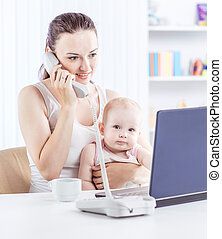 young mother and baby using laptop to communicate with grandma via Skype,
