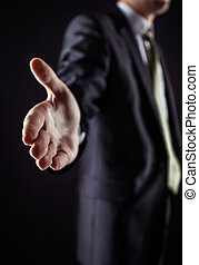 concept of partnership in business: a businessman holds out his hand forward for a handshake