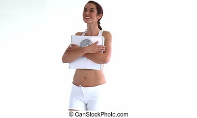 Smiling hispanic woman holding a scale
