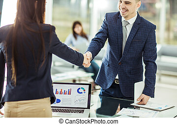 shaking hands with financial partners near the workplace
