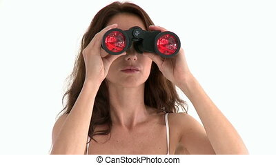Serious hispanic woman looking through binoculars against a...