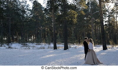 Young wedding couple walking in snowy pine forest wintertime...