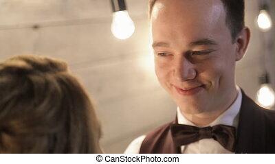 Happy groom look at his bride with elegant bouquet indoor....