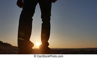 freedom. Man stands on a cliff sunset silhouette hand in lifestyle the sides