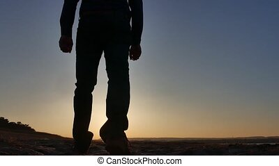 freedom. Man stands on a cliff sunset silhouette hand in the...