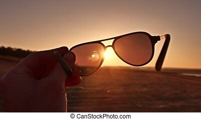 travel. Hand holds sunglasses at sunset nature lifestyle -...