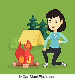 Woman roasting marshmallow over campfire. - Woman sitting...
