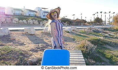 Happy young woman on vacation with a suitcase. Travel...