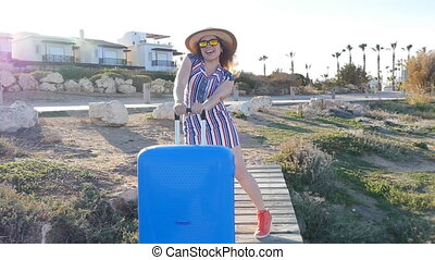Happy young woman on vacation in a hat with a suitcase