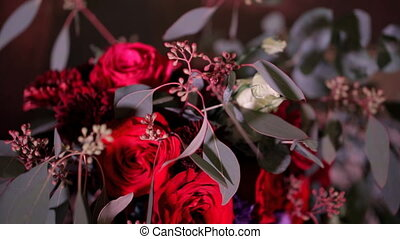 Flashes of camera reflected on red bouquet of roses...