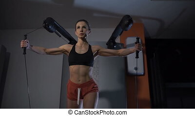 Girl athletic training shoulders in the gym.