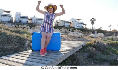 Happy young woman on vacation in a hat with a suitcase....