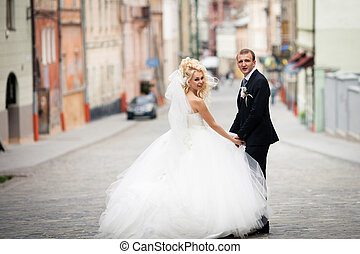 Newlyweds turn around walking down the street
