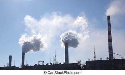 White clouds in the sky from pipes of industrial plant -...