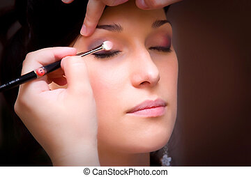 make up artist makeing a make up with an eye brush