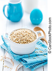 Rolled oats on white wooden background