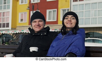 Smiling man and woman on the street are holding closed cups....