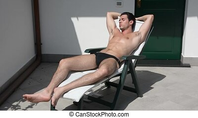 Young Man Sunbathing and Using Cell Phone - Shirtless Young...