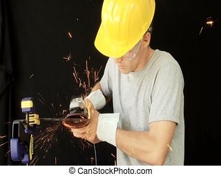 Grinding - Man using a small angle grinder to sharpen a...