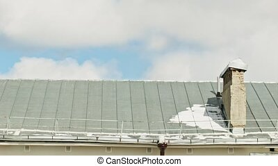 The ice melts on the roof at spring sunny day, time-lapse