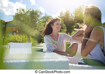 Two female friends talking at cafe table outside