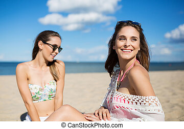 Happy beautiful girl sitting on beach with friend looking...