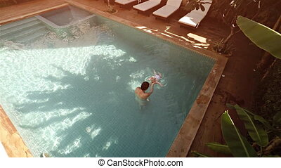 Overlooking Perspective of Baby Swimming with Mommy's Help -...