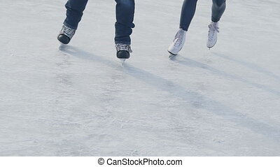 At the rink lovers young man and woman skate and laugh happily.